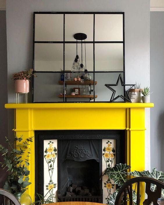 un camino vintage con piastrelle floreali su ogni lato e una mensola del camino giallo solare sembra molto raffinato e di ispirazione vintage