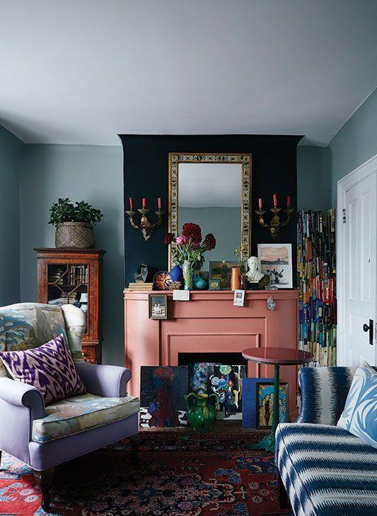 un luminoso soggiorno stravagante con un caminetto rosa e opere d'arte colorate sembra insolito e molto accattivante