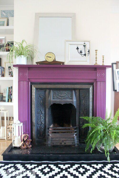 un caminetto vintage con una mensola viola intorno, alcune piante in vaso, lanterne a candela e specchi