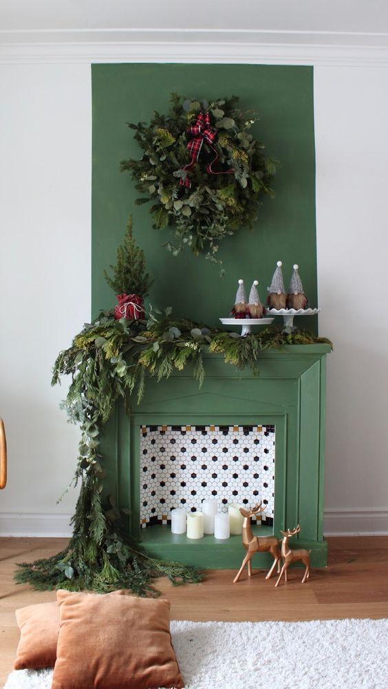 un caminetto verde non funzionante con piastrelle esagonali e candele all'interno, con rigogliosi sempreverdi per Natale