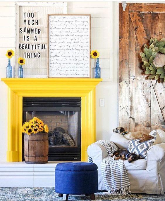 un caminetto giallo sole, un pouf blu audace e bottiglie blu con girasoli per rendere lo spazio più audace