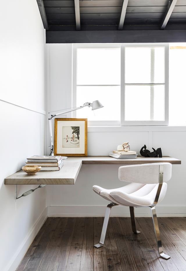 un angolo minimalista dell'home office con una scrivania angolare galleggiante, una sedia stravagante e libri e un'elegante lampada industriale