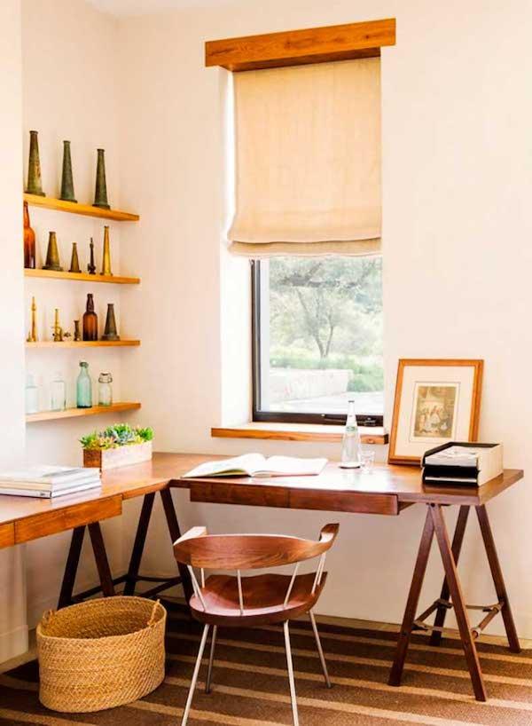 un accogliente angolo rustico da casa con una grande scrivania angolare a cavalletto, scaffali aperti, un cestino e una sedia in legno più sfumature