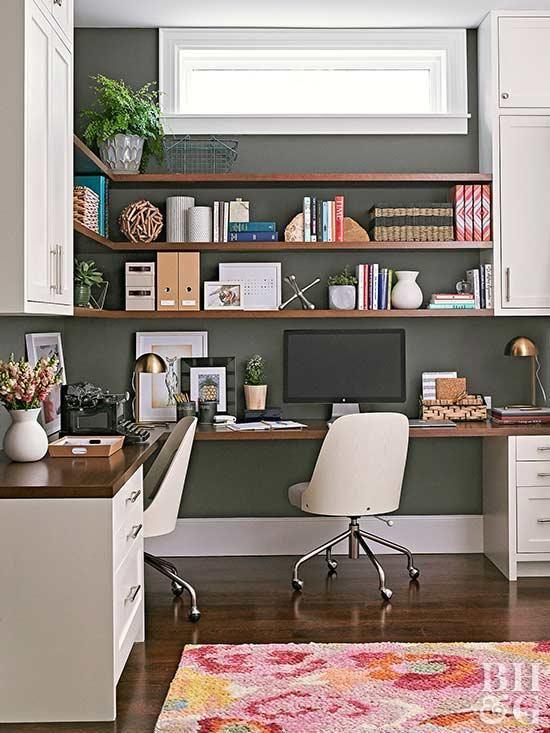 un moderno home office della metà del secolo con un muro nero, una scrivania ad angolo e scaffali aperti con contenitori chiusi più eleganti sedie bianche