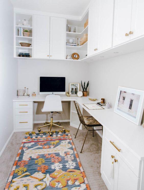 un moderno ufficio a casa della metà del secolo in bianco, con una scrivania ad angolo e armadi, armadi sopra la scrivania e un tappeto luminoso e divertente