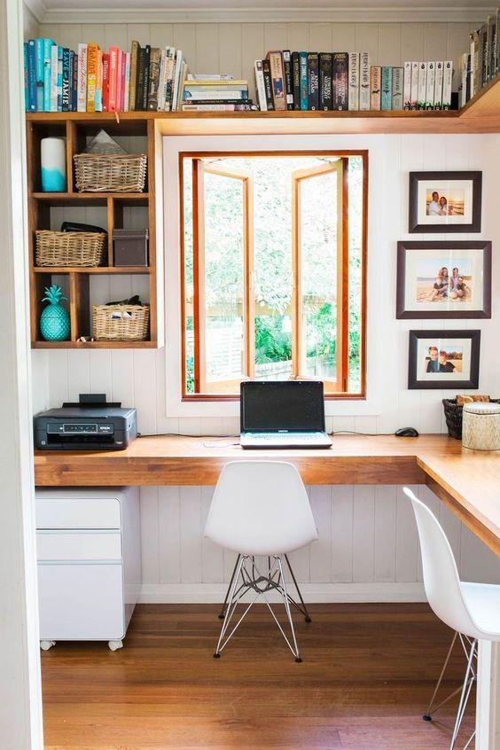 un moderno ufficio rustico con una scrivania ad angolo in legno, scaffali aperti, sedie bianche e molti libri e foto