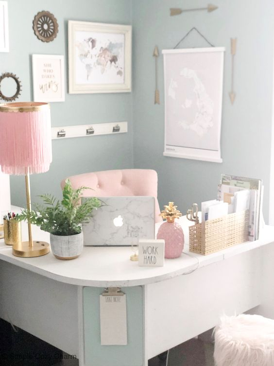 un ufficio da ragazza pastello con una scrivania ad angolo curva, accessori rosa e una sedia rosa e tocchi d'oro per più chic