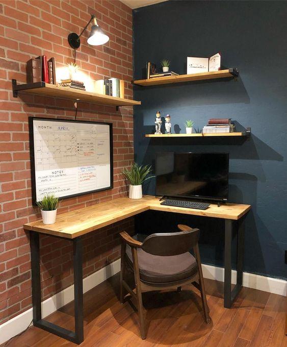 un moderno angolo per l'home office industriale con una scrivania angolare in legno e alcuni scaffali, una comoda sedia e lampade