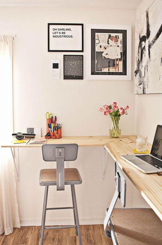 un moderno ufficio industriale con una scrivania galleggiante in legno, sgabelli in metallo, una galleria a muro in bianco e nero e fiori