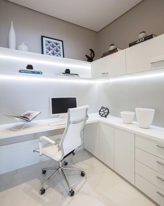 un home office minimalista con una scrivania ad angolo e alcuni armadietti sotto la superficie, scaffali e armadietti illuminati sopra
