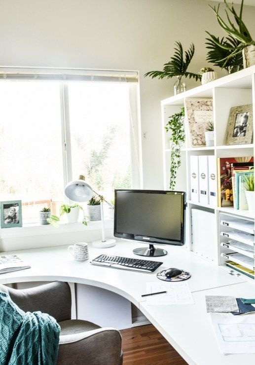 un elegante ufficio da casa contemporaneo in bianco, con una scrivania ad angolo curva e un contenitore aperto, una sedia comoda e un po 'di verde