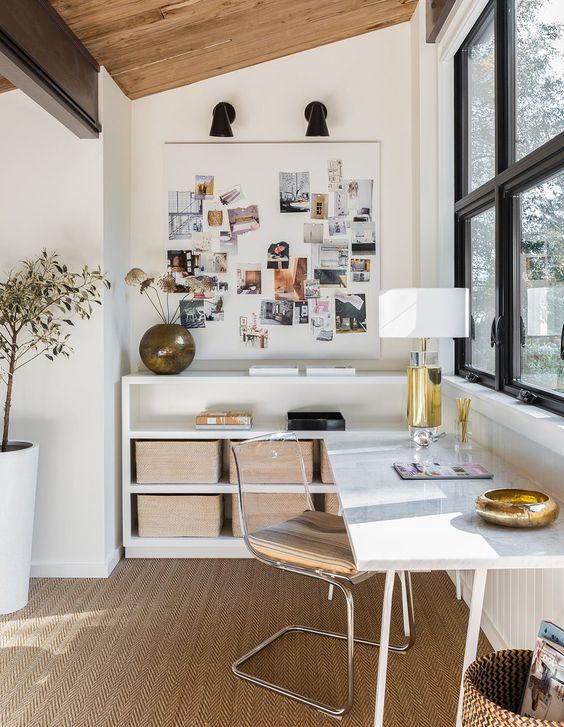 un ufficio domestico elegante e raffinato con una scrivania ad angolo e contenitori a giorno, un tappeto di iuta e una sedia in acrilico è molto chic