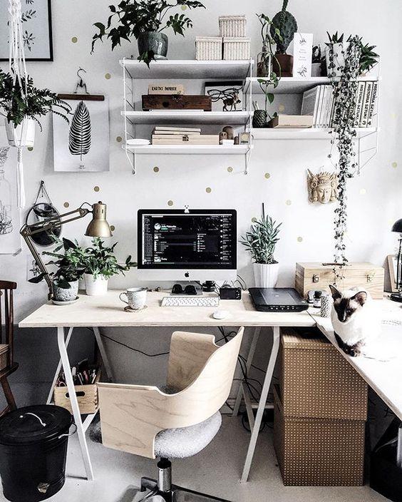 un elegante ufficio in casa scandinavo con una scrivania ad angolo a cavalletto, scatole, vegetazione, un muro a pois e una sedia in compensato