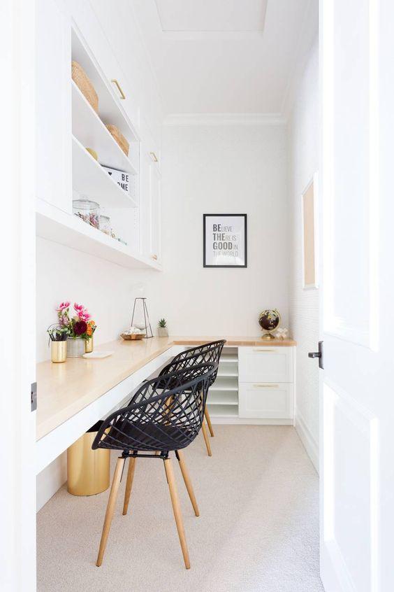 un minuscolo ufficio domestico bianco con una scrivania d'angolo condivisa e armadietti sotto la superficie, un grande armadio aperto e sedie intrecciate nere