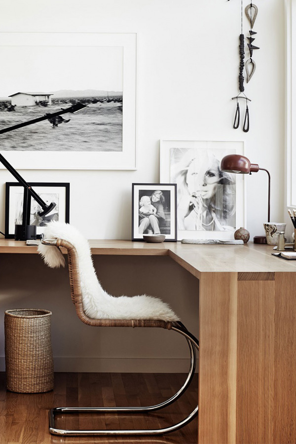 un angolo per l'home office scandinavo con una scrivania angolare galleggiante, una galleria a muro, una sedia in rattan e un cesto più un po 'di pelliccia sintetica