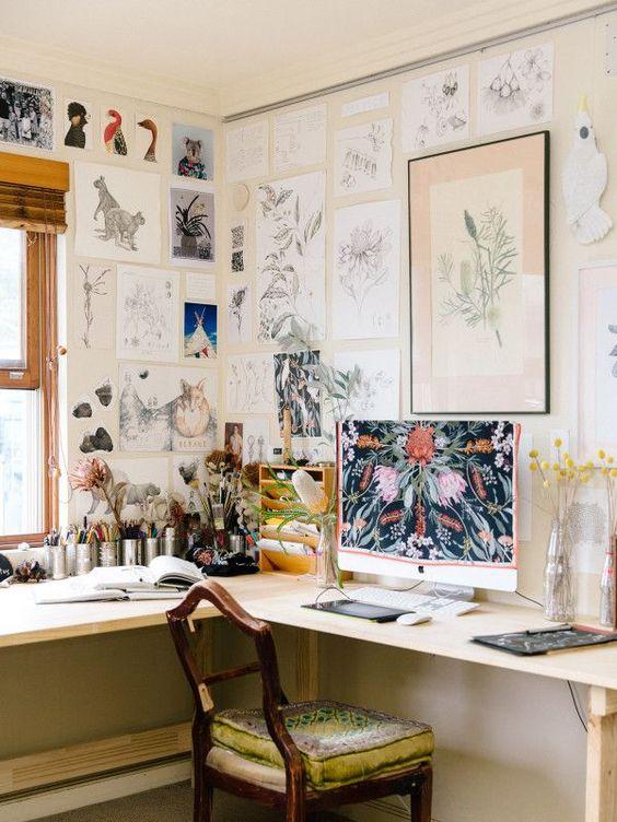 un home office vintage con una scrivania ad angolo, una sedia vintage, una grande galleria a muro che copre le pareti e una finestra