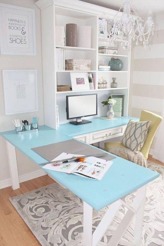 un ufficio in casa d'epoca con una scrivania d'angolo blu e un mobile contenitore su un lato, una sedia gialla e un lampadario di cristallo glam