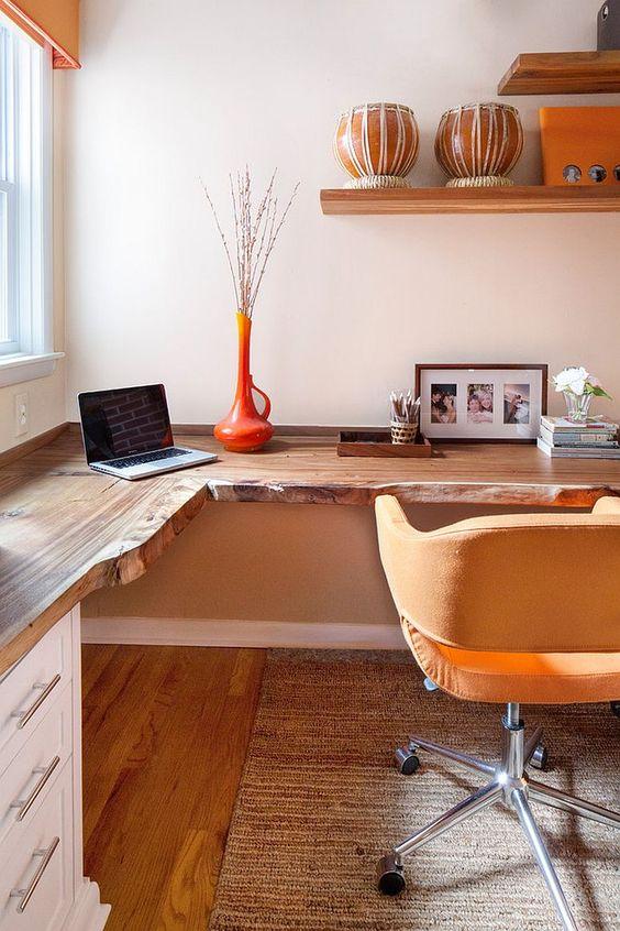 un ufficio in casa dai colori caldi con una scrivania ad angolo dal vivo, una sedia gialla, scaffali aperti e un vaso arancione