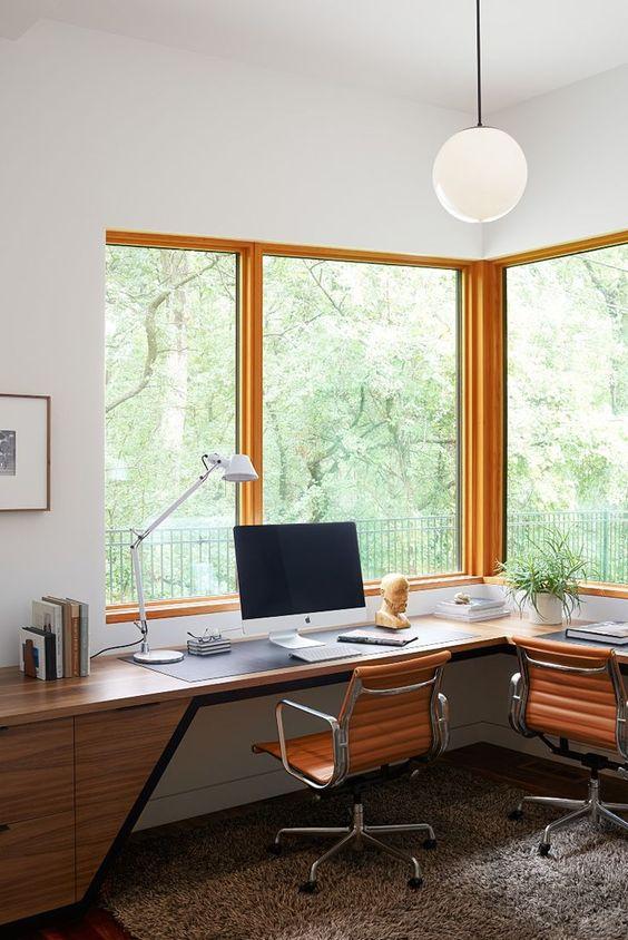 un elegante home office moderno della metà del secolo con un'elegante scrivania ad angolo in legno, sedie in pelle e ampie finestre per godersi il panorama