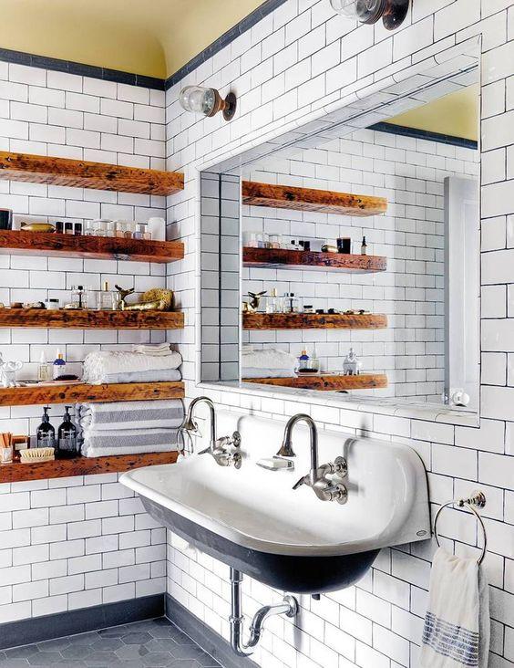 Gli scaffali aperti in lastre di legno ammorbidiscono il bagno industriale vintage rendendolo più caldo