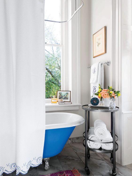 un carrello rotondo in metallo e vetro nero è un'idea elegante per mostrare alcuni decori e riporre gli asciugamani