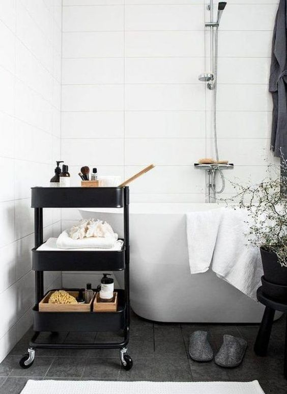 un carrello IKEA nero utilizzato per la conservazione in un bagno scandinavo è un pezzo elegante da provare