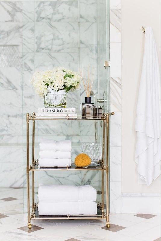 un raffinato carrello in oro e vetro è una splendida opzione per un bagno sofisticato e chic