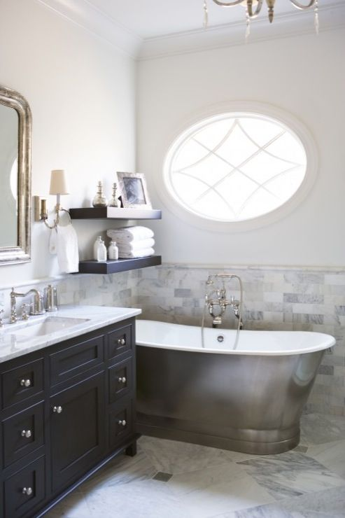 mensole fluttuanti scure su una vasca da bagno rivestita in metallo vintage e una vanità nera abbinata per uno spazio raffinato