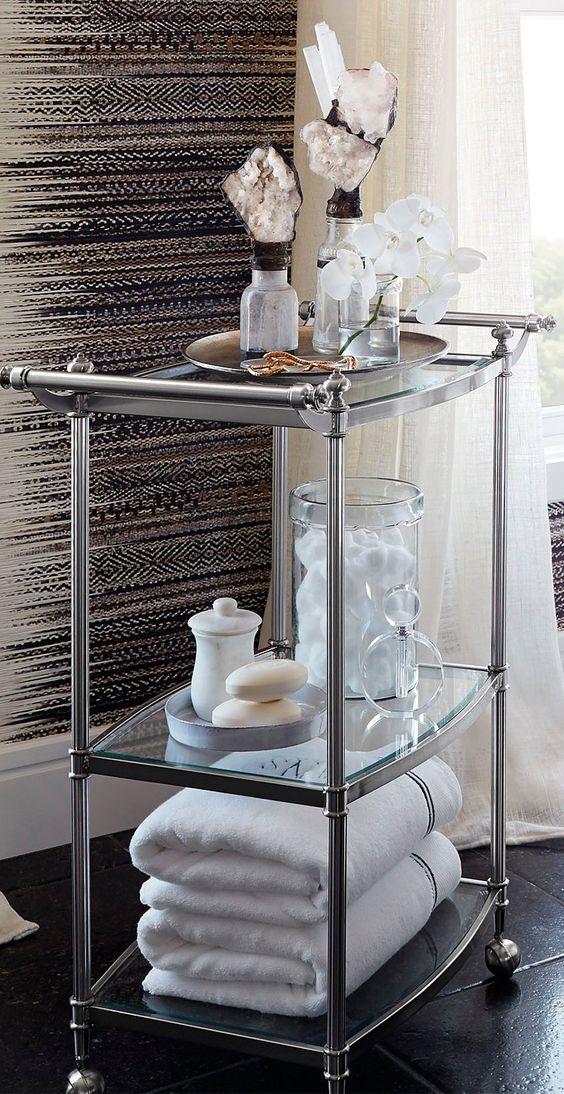 un raffinato carrello in acciaio inossidabile e vetro è un elegante pezzo di stoccaggio con molti oggetti e alcuni decori