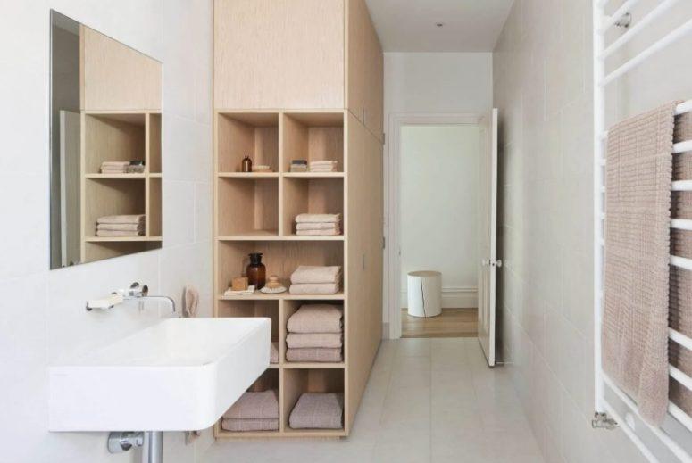 un bagno minimalista neutro che mostra un grande armadio per lo stoccaggio che finisce con scaffali aperti per un maggiore comfort