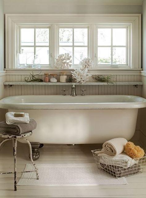 un bagno costiero shabby chic con una mensola galleggiante aperta sopra la vasca che consente la visualizzazione di decorazioni