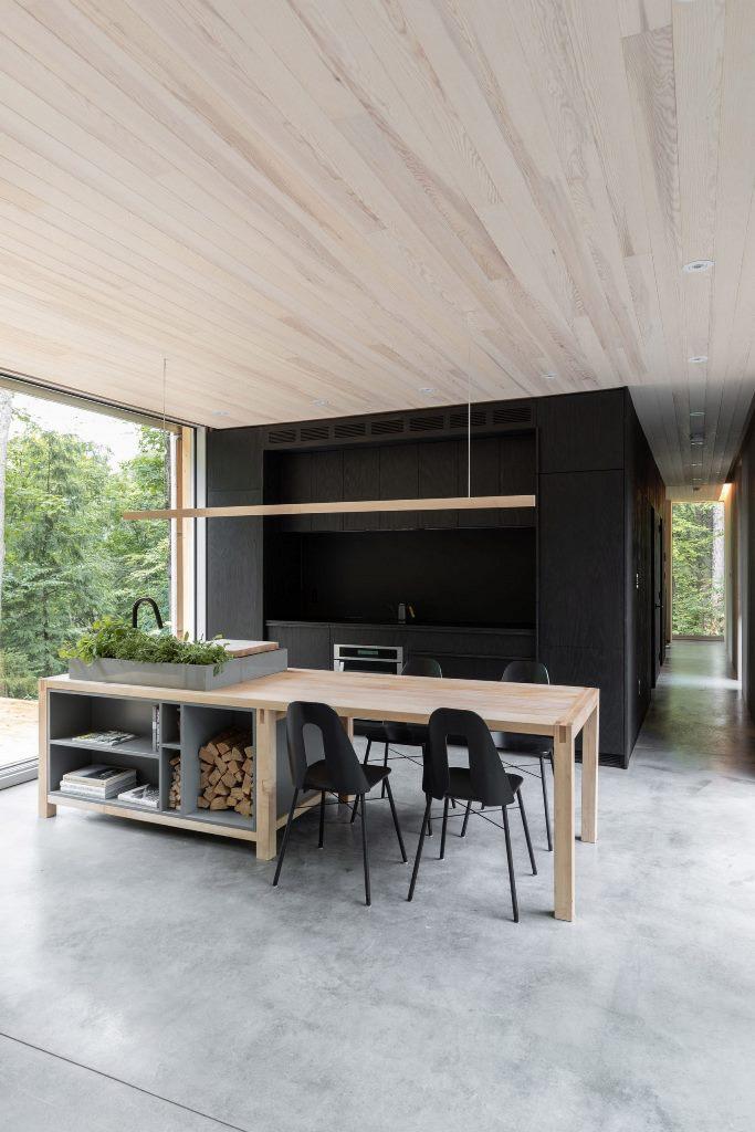 La cucina è nera, c'è un'isola in legno e pietra che funge anche da tavolo da pranzo