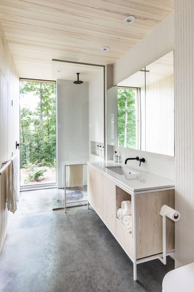 Il bagno è completamente neutro, con piastrelle bianche e compensato neutro e una splendida vista sulla foresta