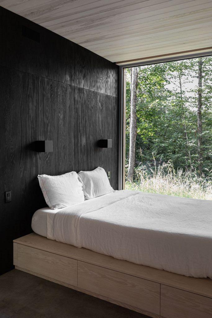 La camera da letto è realizzata con pareti nere, un letto a piattaforma con contenitore e una parete vetrata