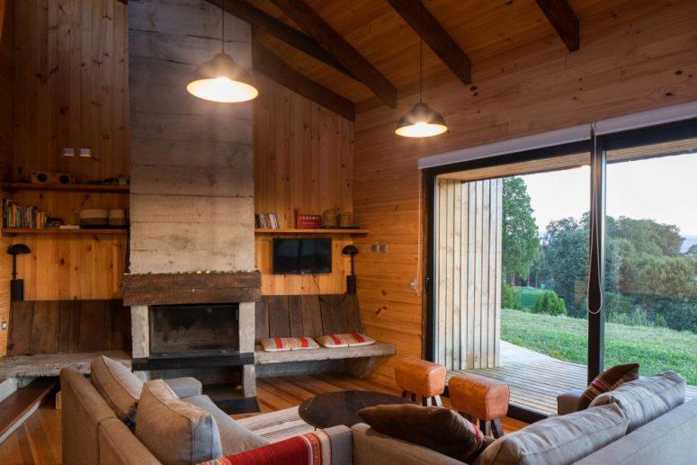 Anche il soggiorno è rivestito in legno, ci sono travi in legno e un focolare oltre a tessuti folk boho luminosi