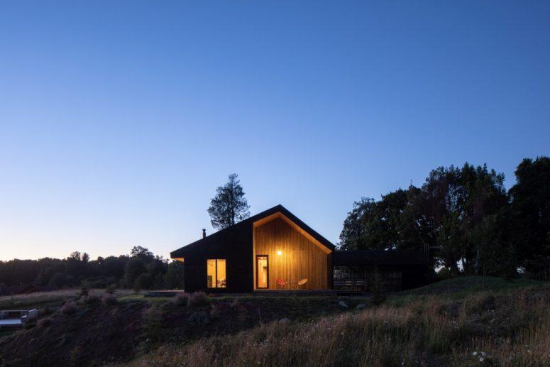 L'esterno scuro e il caldo interno in legno si completano a vicenda e avvicinano la casa all'ambiente circostante