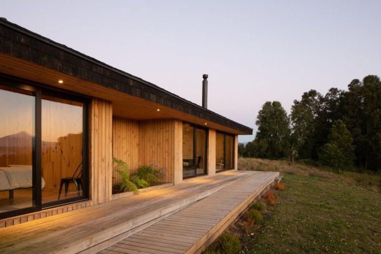 Il ponte in legno che collega le camere da letto viene gradualmente abbassato fino a diventare a filo con il giardino