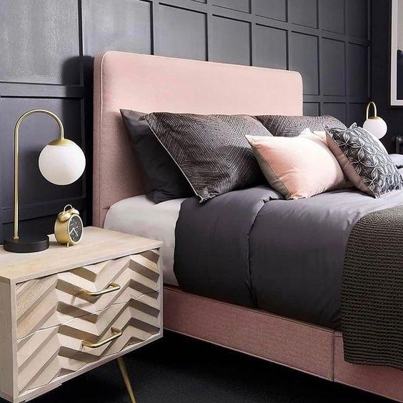 una camera da letto chic con pannelli neri, un letto rosa, biancheria da letto nera e rosa e comodini chevron più tocchi d'oro