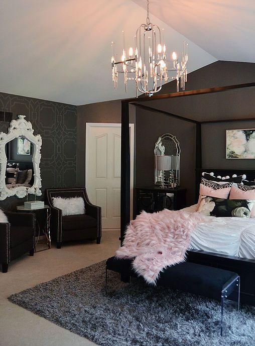 una camera da letto chic e raffinata con pareti nere, un letto nero e altri mobili per sedersi, un accattivante lampadario di cristallo e biancheria da letto rosa