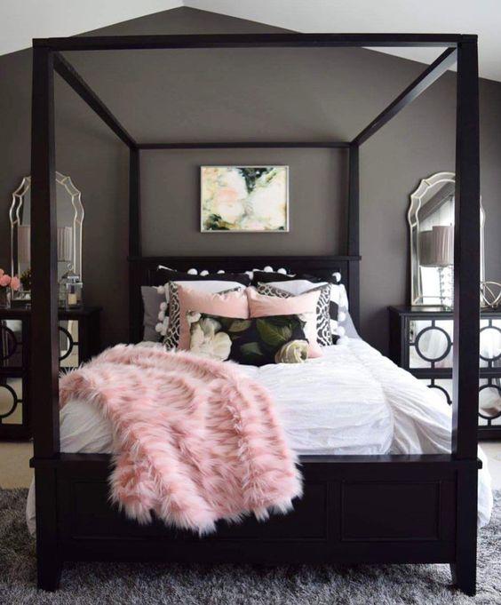 un'elegante camera da letto grigia con mobili neri, comodini a specchio, biancheria da letto arrossata e nera e tappeti a strati