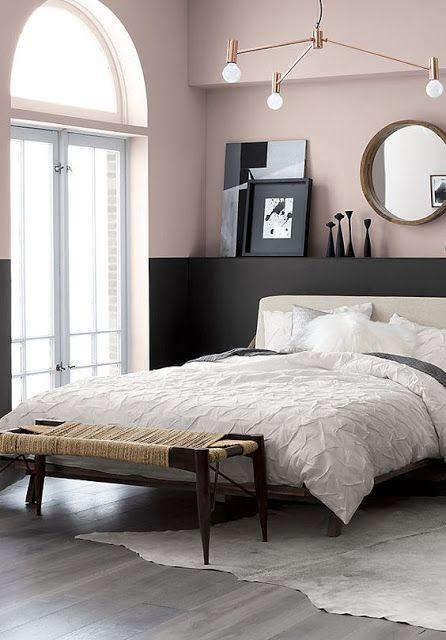una camera da letto moderna chic con fard color block e pareti nere, un letto neutro, un lampadario moderno della metà del secolo e una panca intrecciata