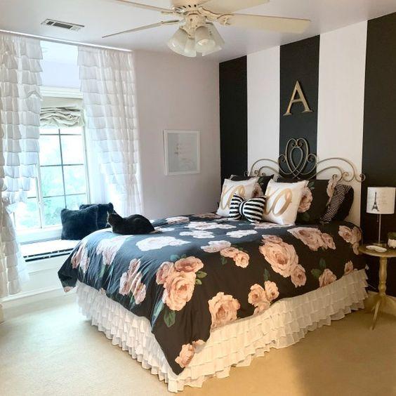 una camera da letto glam e raffinata con un muro con accento a strisce, biancheria da letto floreale nera, tende bianche con volant e mobili raffinati