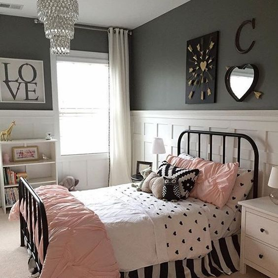 una camera da letto glam con pareti nere, pannelli bianchi, un letto nero, biancheria da letto rosa e nera, un lampadario di cristallo e cuori