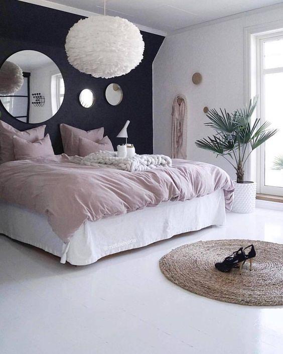una camera da letto moderna ma romantica con un muro di accento nero, mobili bianchi e una soffice lampada a sospensione più biancheria da letto arrossata