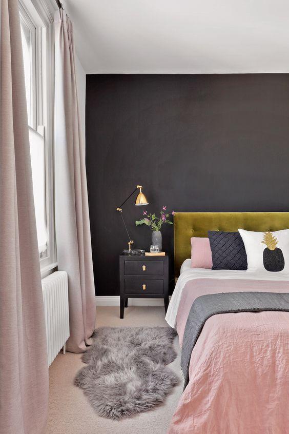 un'elegante camera da letto moderna con un muro nero, un letto in velluto senape, comodini neri, lenzuola arrossate e tocchi dorati