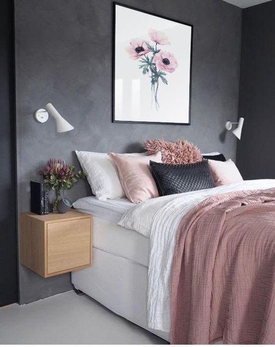 una camera da letto elegante e semplice con pareti nere, un letto bianco, biancheria da letto rosa e nera, comodini galleggianti e applique