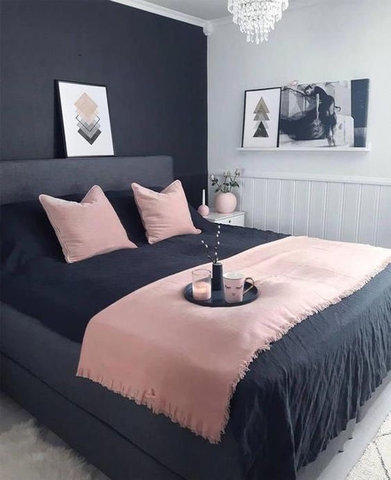 una piccola camera da letto moderna con una parete nera, un letto nero, biancheria da letto rosa e nera e un lampadario di cristallo