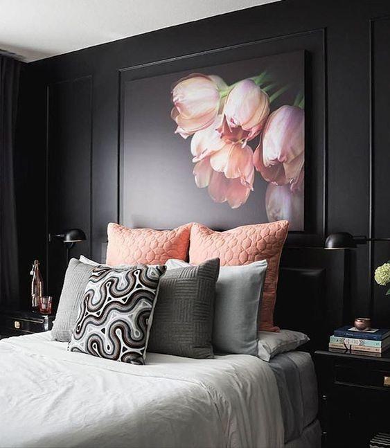 una raffinata camera da letto lunatica con pareti nere, mobili neri, biancheria da letto rosa e grigia e un'opera d'arte floreale rosa