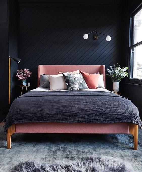 una piccola camera da letto moderna con pareti in legno nero, un letto rosa e lenzuola grigie e rosa, vegetazione e fiori