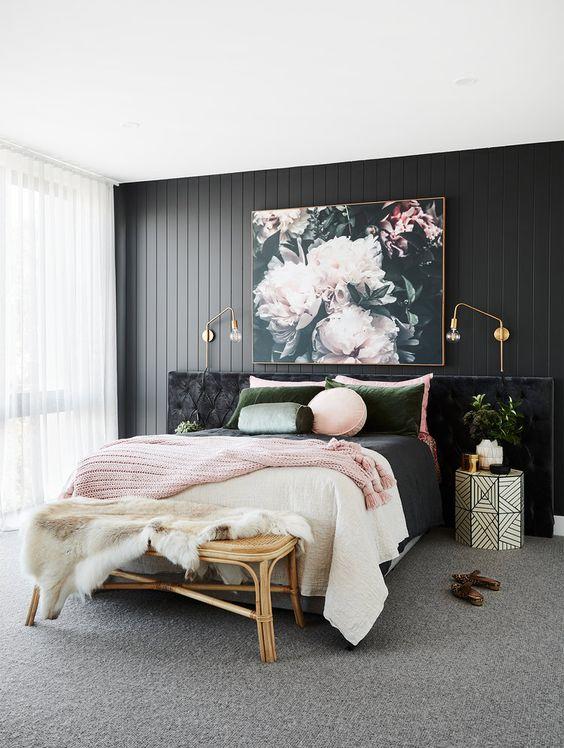 una camera da letto raffinata con un muro di accento in legno nero, un letto imbottito nero, biancheria da letto rosa e verde e una bellissima opera d'arte floreale